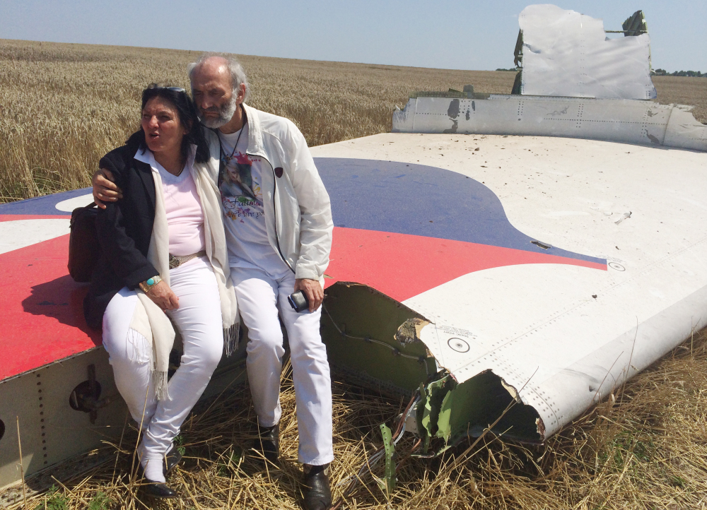 Jerzy Dyczynski and Angela Rudhart-Dyczynski whose daughter, 25-year-old Fatima, was a passenger on Malaysia Airlines flight MH17, sit on part of the wreckage of the crashed aircraft in Hrabove, Ukraine, on Saturday. The couple who live in Perth, Australia, crossed territory held by pro-Russian rebels to reach the wreckage-strewn farm fields outside the village of Hrabove. They last spoke to Fatima shortly before she boarded the flight for Kuala Lumpur in Amsterdam on July 17. The Associated Press