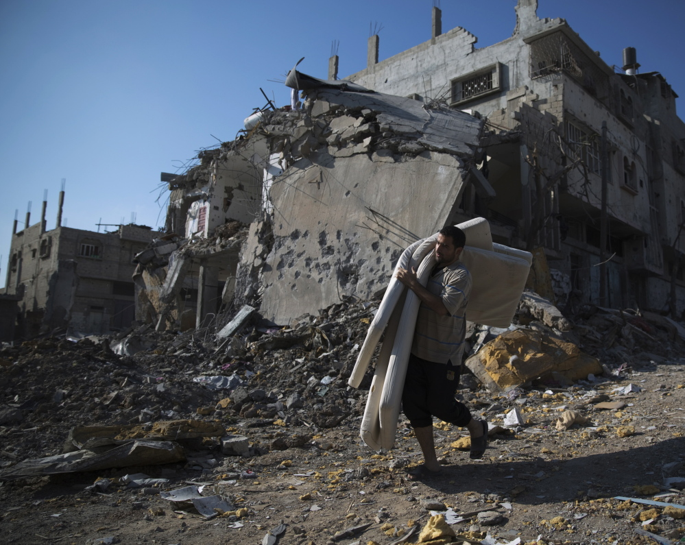 A Palestinian man carries salvaged belongings from damaged buildings in the Shejaia neighborhood of Gaza City on Sunday. Witnesses said the area was heavily hit by Israeli shelling.