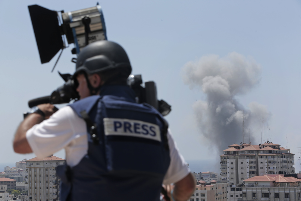 A news cameraman films at a live position as in the background smoke rises from an Israeli strike in Gaza City, Sunday.