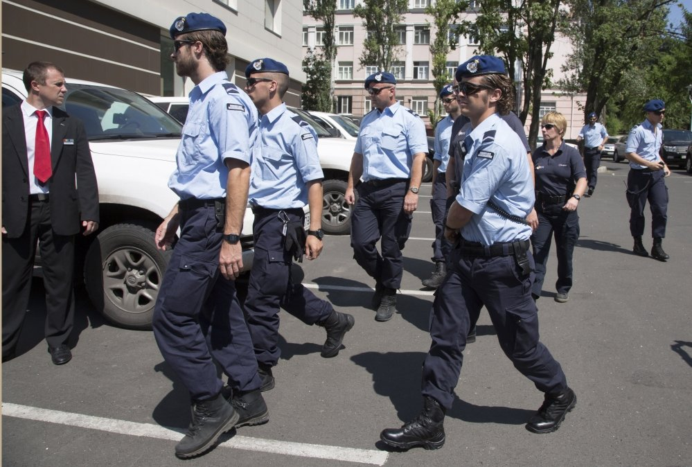 Dutch policemen walk in the city of Donetsk, eastern Ukraine Sunday.