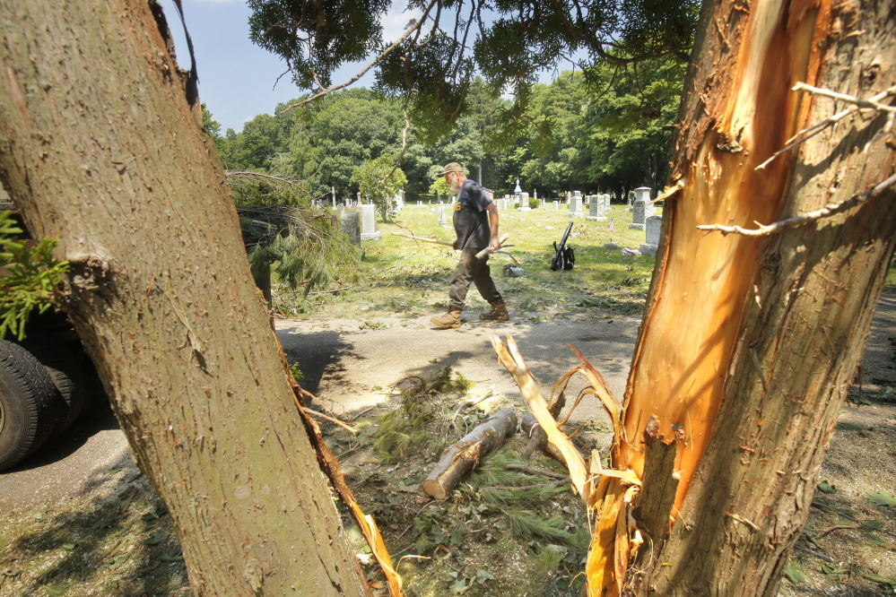 Doug Briley of Chase Tree Service cleans up debris Wednesday in the First Parish Cemetery in York after a microburst hit the York Village area July 15. In 2010, a microburst hit the same part of town, causing in $100,000 in damage.