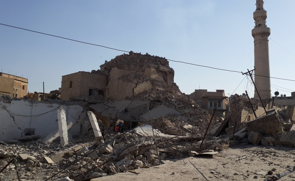 People inspect the destroyed old Mosque of The Prophet Jirjis in central Mosul, Iraq, on Sunday. The revered Muslim shrine was destroyed on Sunday by militants.