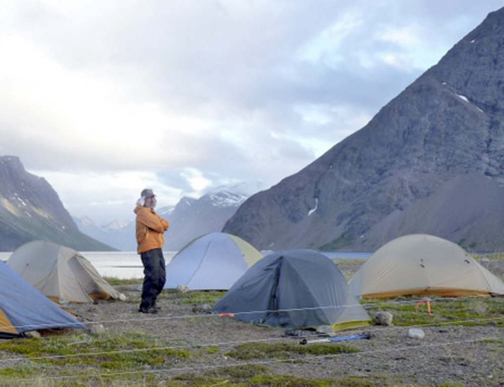 A fellow hiker took this photo of Matt Dyer at the campsite in Canada before he was attacked by a polar bear after dark in July 2013. Dyer's group used an electrified fence, in foreground, at the site to try to prevent bear attacks, but the bear broke through it. Dyer now believes it's inadequate to sleep behind an electrified bear fence.