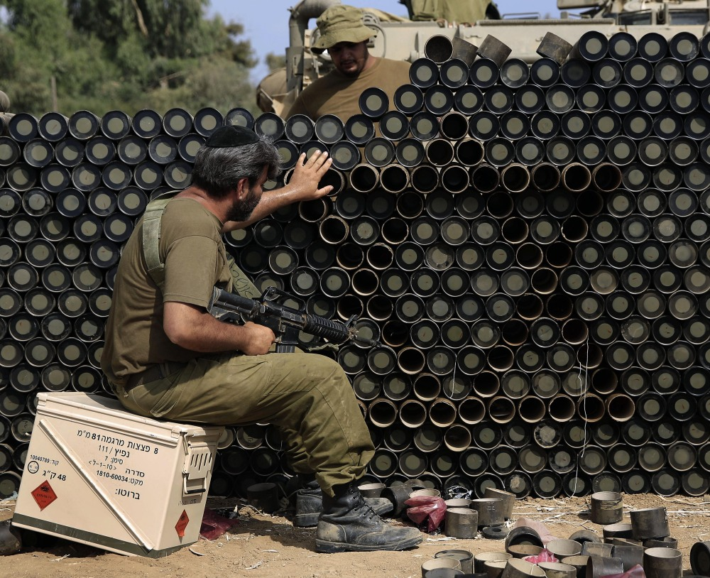 An Israeli reserve soldier makes a Star of David pattern from cardboard mortar shell boxes near the Israel-Gaza border on Monday. A truce between Israel and Hamas militants in Gaza remains elusive as Secretary of State John Kerry continues to work for a cease-fire.