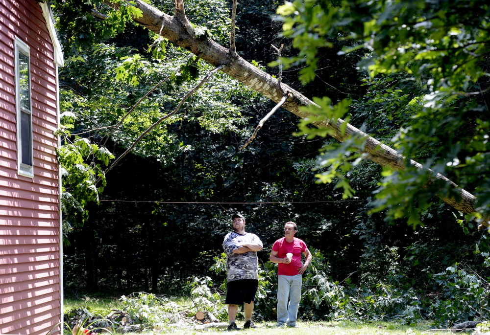 Josh St. Pierre, left, of Limington looks over the damage done by Monday's storm at his home in Limington, with his uncle Dave Vastille of Saco.