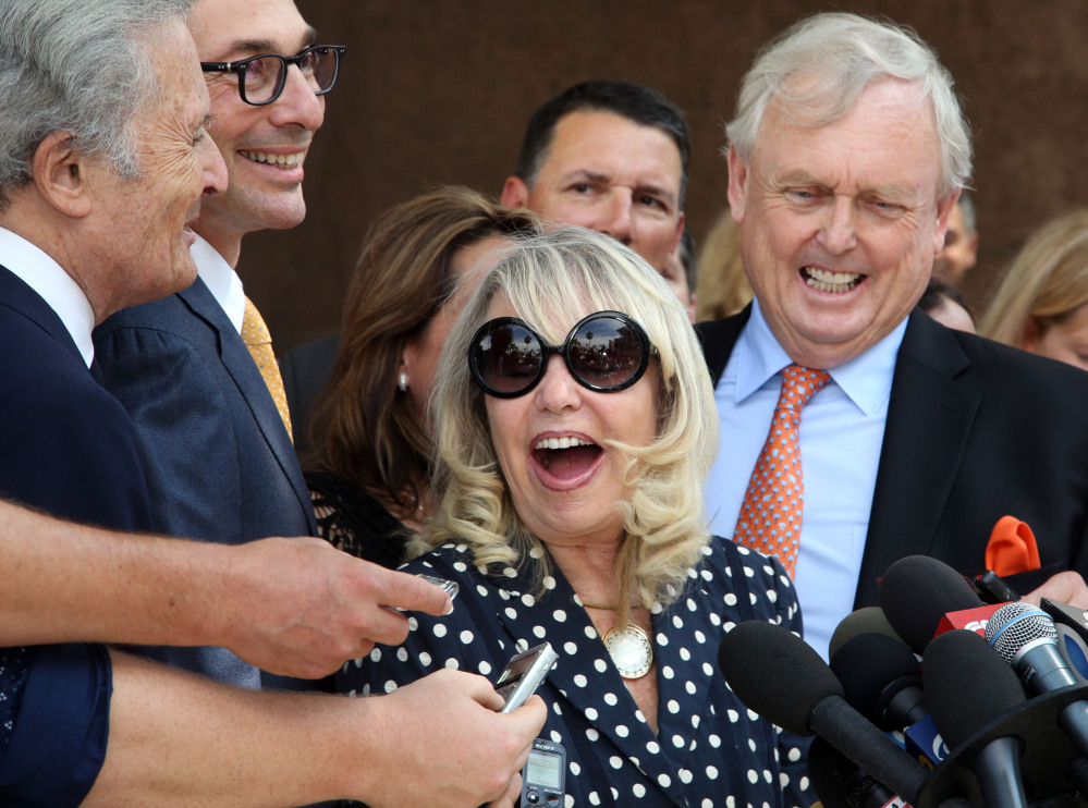 With her attorney Pierce O'Donnell, right, Shelly Sterling, center, talks to reporters after a judge ruled in her favor and against her estranged husband, Los Angeles Clippers owner Donald Sterling, in his attempt to block the $2 billion sale of the NBA basketball team, outside Los Angeles Superior Court, Monday.