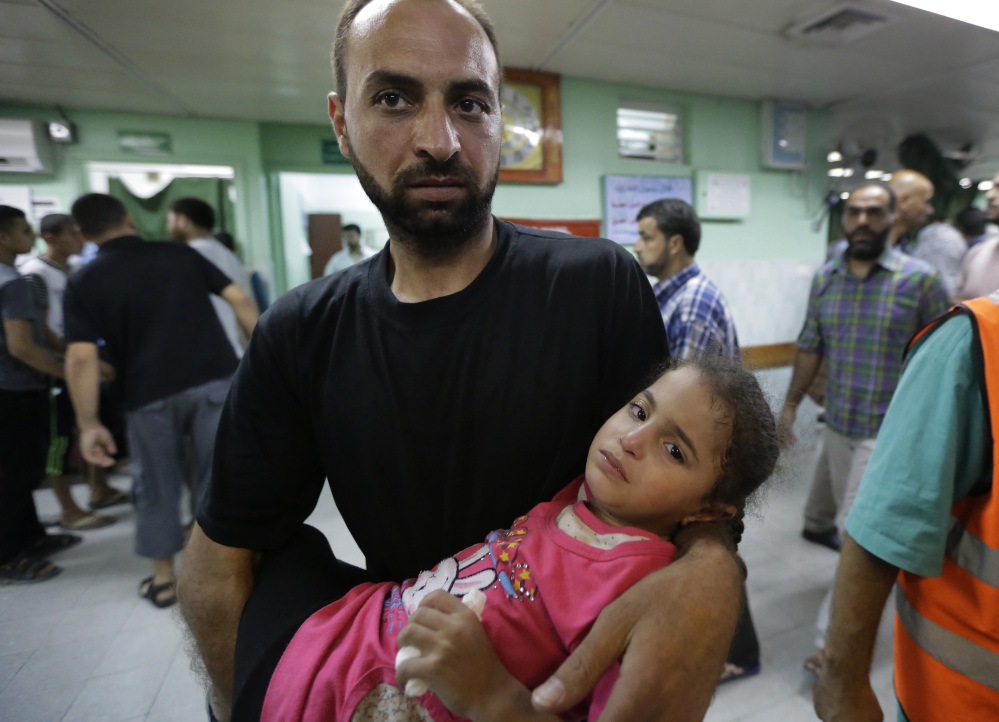 A Palestinian man carries a girl who was wounded in an Israeli strike in the Jebaliya refugee camp into the emergency room of the Kamal Adwan hospital, in Beit Lahiya, northern Gaza Strip, on Tuesday.