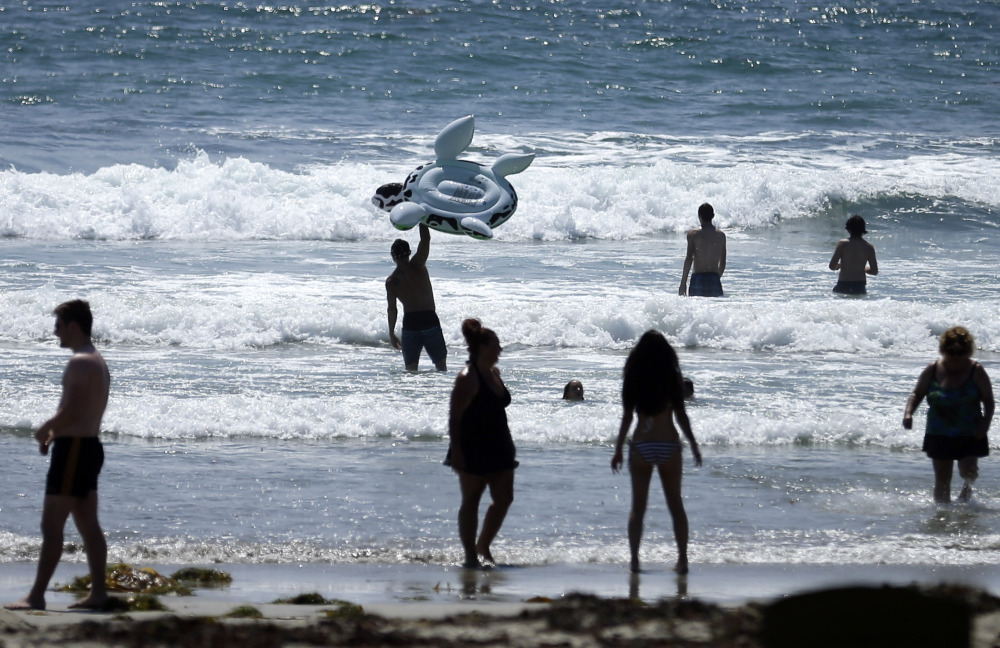 FILE - This, June 24, 2014, file photo shows people swimming on a sunny day at Mission Beach in San Diego. Stop sunbathing and using indoor tanning beds, the acting U.S. surgeon general warned in a report that cites an alarming 200 percent jump in deadly melanoma cases since 1973. (AP Photo/Gregory Bull, File)