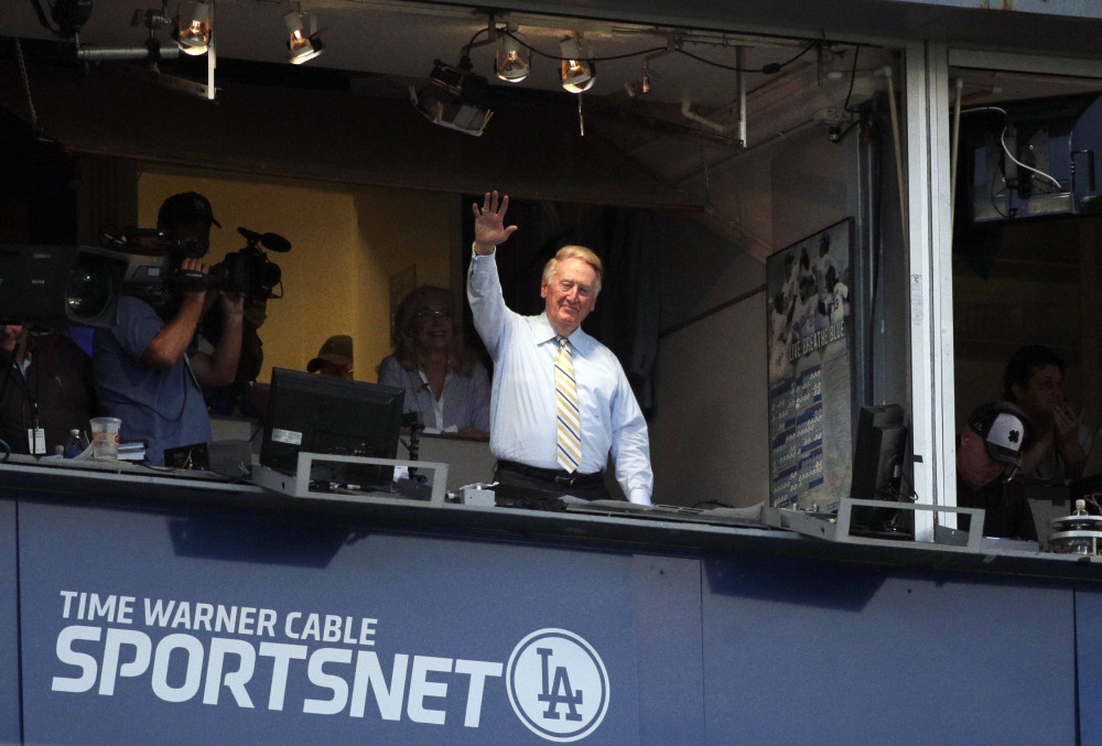 Broadcaster Vin Scully acknowledges the crowd at Dodger Stadium during a baseball game between the Los Angeles Dodgers and the Atlanta Braves on Tuesday.