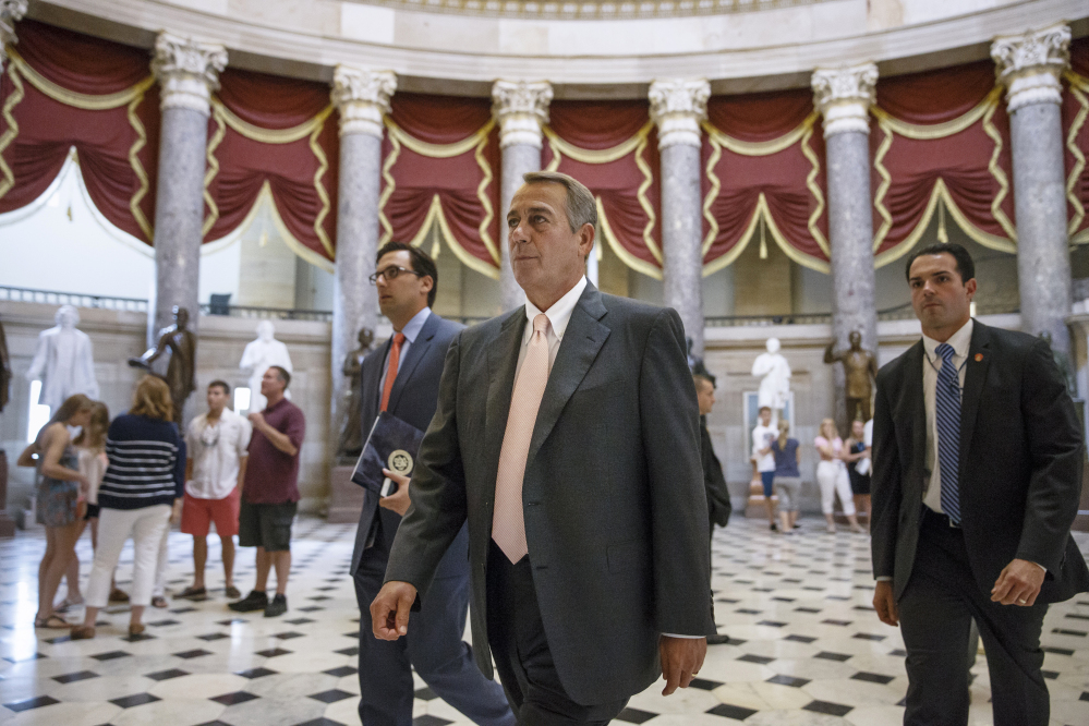 House Speaker John Boehner walks to the House chamber Wednesday as lawmakers prepare to move on legislation to authorize a lawsuit that accuses President Obama of exceeding his powers in enforcing the Affordable Care Act.