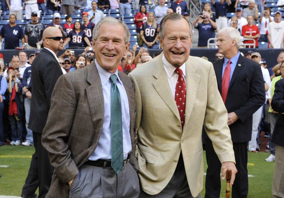 George H.W. Bush, right, and George W. Bush attend a Texans NFL game in Houston in 2009. The elder Bush is one of the few recent presidents not to have written a memoir.