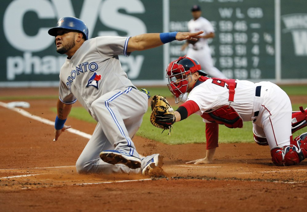 Blue Jays outfielder Melky Cabrera slides safely into home past Red Sox catcher Christian Vazquez, scoring on a fielder's choice grounder by Juan Francisco in the first inning Fenway Park on Wednesday.