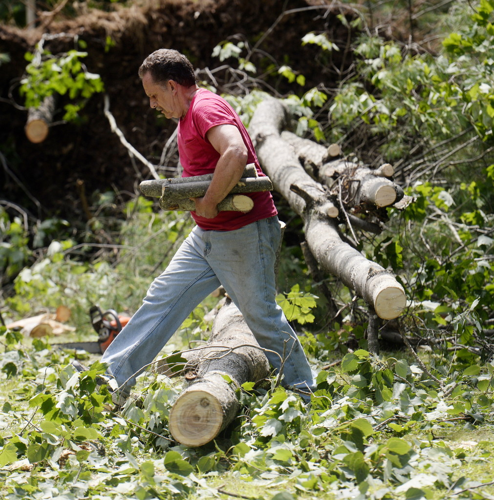 Dave Vastille of Saco cleans up debris at the home of his nephew Josh St. Pierre in Limington on Tuesday, a day after a tornado touched down in the York County town.