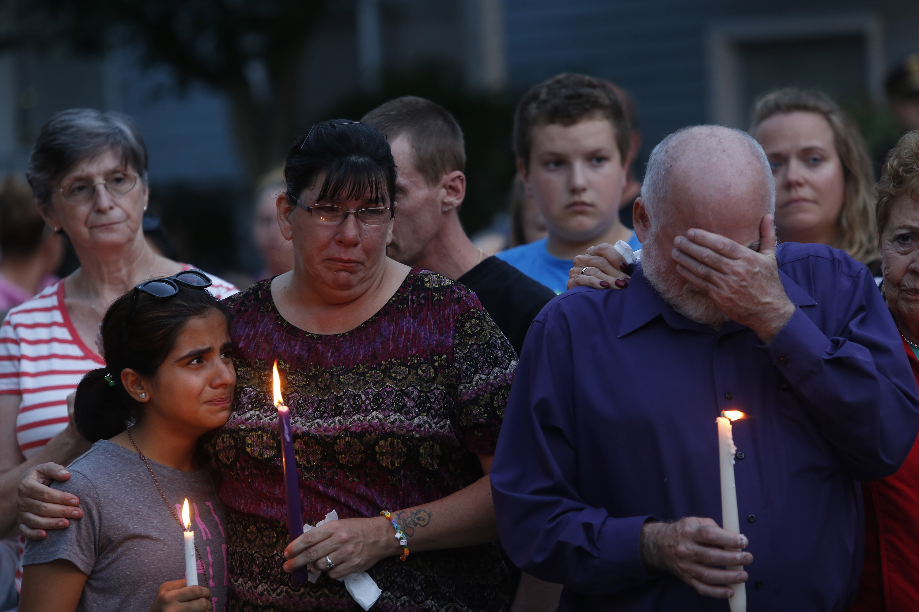 "Becca Garland comforts her neighbor Youna Karim, 12, during a vigil for the Smith family at the RiverView apartments in Saco on Tuesday night, while Joel Smith's father, Steve Smith, covers his face.  Garland said, ""I was her best friend here,"" speaking of Heather Smith, one of the victims. ""We had a barbeque on Saturday night and I kissed her and told her 'I love you and I will see you tomorrow.'"""