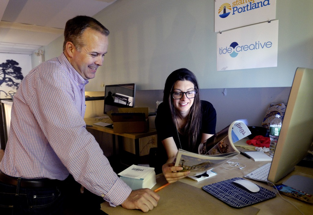 J Sandifer and Liz Kirby of Tide Creative look over ads the company placed in a magazine recently. Shawn Patrick Ouellette/Staff Photographer
