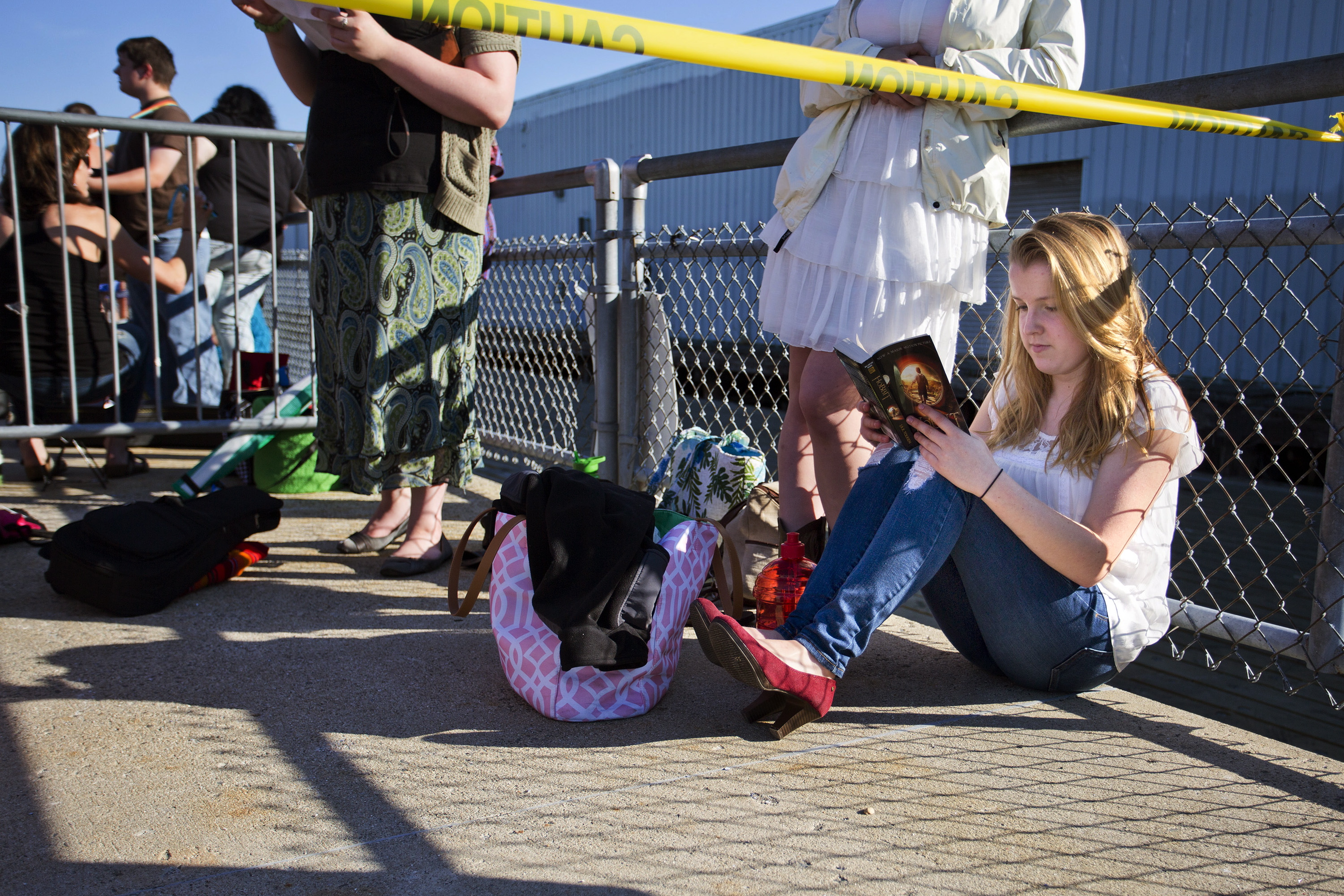 "Abigail Day, 17, of Cornish, reads a book while waiting to audition for ""American Idol"" at the Maine State Pier on Wednesday. Day, who planned to sing ""I See Fire"" by Ed Sheeran, was in line at 2 a.m."