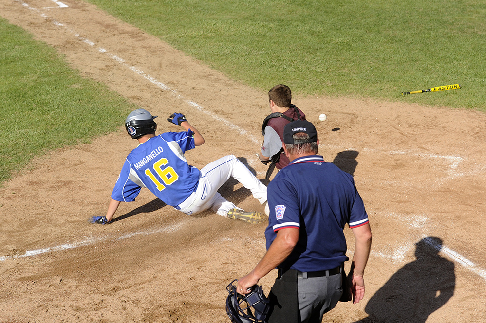 Falmouth's Sam Manganello slides safely into home against Saco's Calvin Christofordat the Hill Street Field on Thursday, July 24, 2014. (Photo by Logan Werlinger/Staff Photographer)