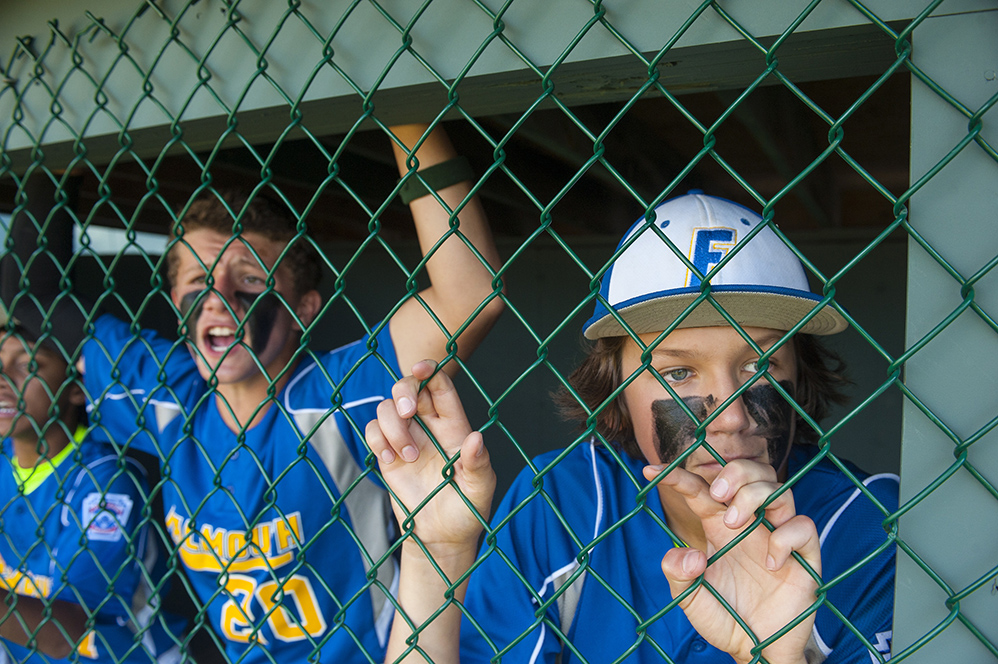 Jackson Quinn grips the fence as he watches his teammates bat at the Hill Street Field on Thursday, July 24, 2014. (Photo by Logan Werlinger/Staff Photographer)