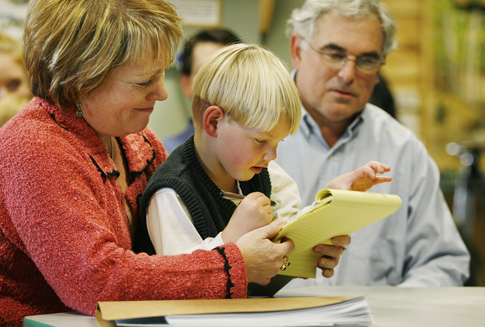 "Jane Riseman and husband Walter look on as their foster child, Michael William Riseman, draws before the start of the adoption ceremony in Portland in 2005. The Risemans adopted Michael, who had been known as ""Baby Jason"" when he was found near death in a Portland motel. Michael was a month old when his parents were arrested in April 2002 at a Motel 6 in Portland. Police say the father, Jason Hann, confessed to killing two other children, a daughter in California and his son in Vermont."