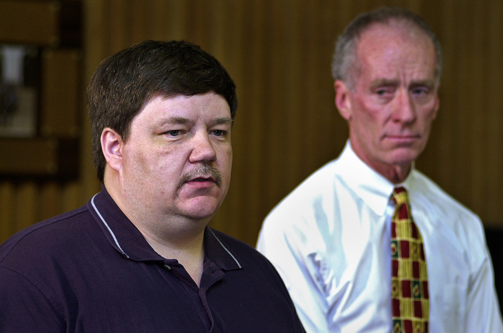In this 2002 file photo, Portland Police Chief Michael Chitwood looks on as Steve Reed of Bowdoinham tells how he recognized the couple that checked into the Motel 6 at Exit 8 where he was the night clerk on duty.