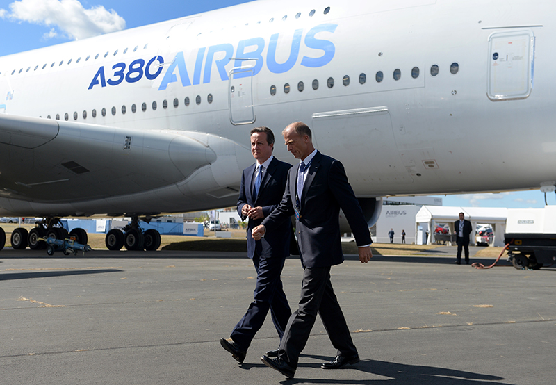 Britain's Prime Minister David Cameron centre, and Tom Enders, the chief executive of Airbus Group, walk by an Airbus A380, during a visit to the 2014 Farnborough Airshow in Hampshire, England, Monday. The Associated Press