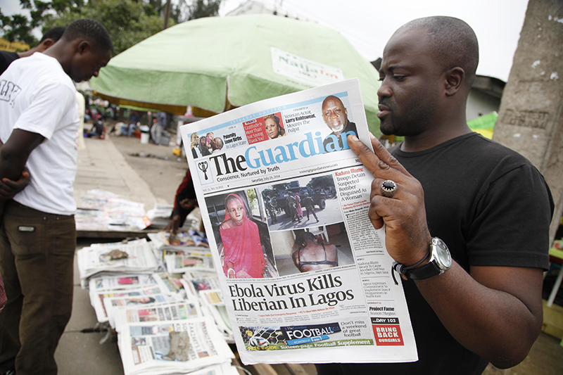 A man reads a local newspaperson a street with the headline Ebola Virus kills Liberian in Lagos, in Lagos Nigeria, Saturday. The Associated Press