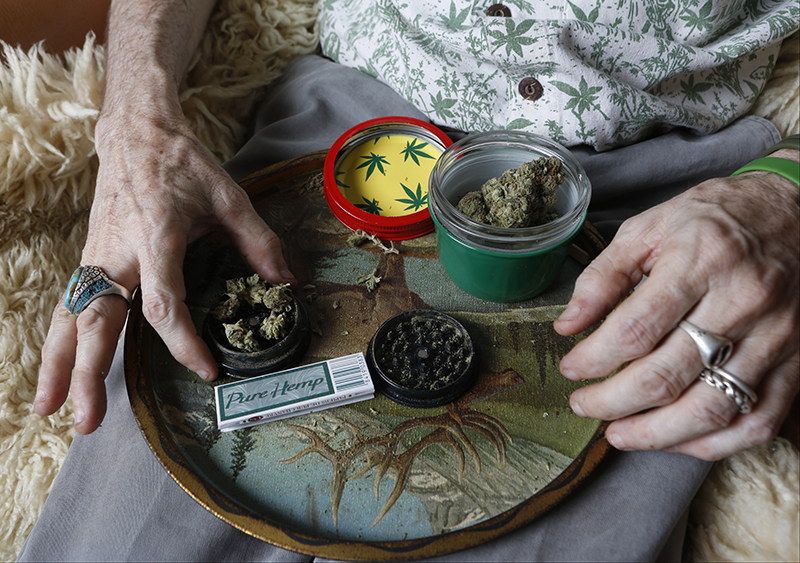 In this April 30, 2014 photo, Bill Britt, who suffers from epileptic seizures and leg pain from a childhood case of polio, prepares a medical marijuana joint at his home in Long Beach, Calif. The Associated Press