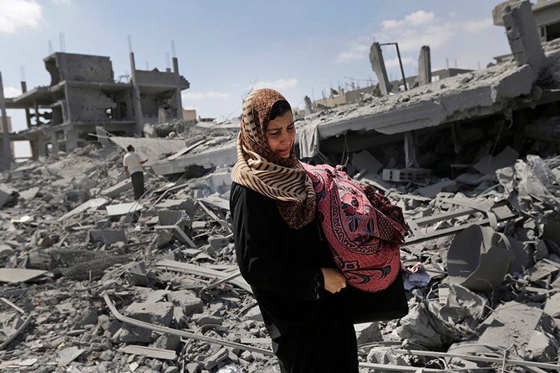 A Palestinian woman carries her belongings past the rubble of houses destroyed by Israeli strikes in Beit Hanoun, northern Gaza Strip, Saturday. The Associated Press