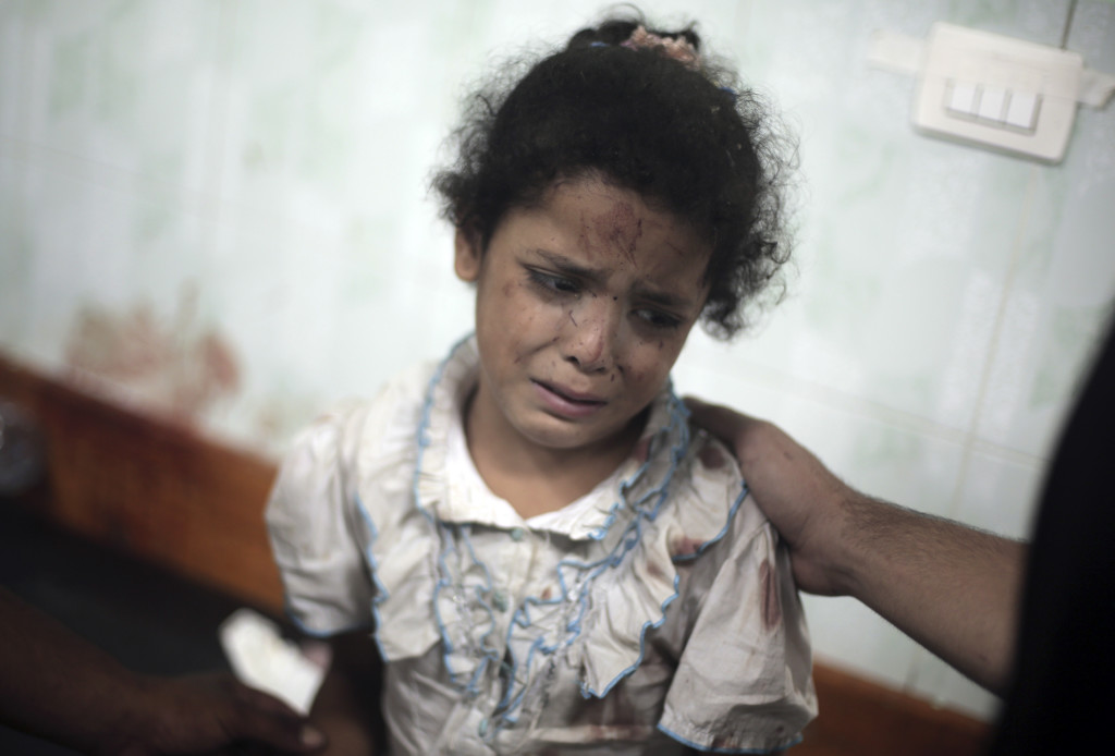 A Palestinian girl cries while receiving treatment for injuries caused when several Israeli tank shells slammed into a crowded U.N. school used as shelter for refugees in the Gaza war early on Wednesday. The Associated Press