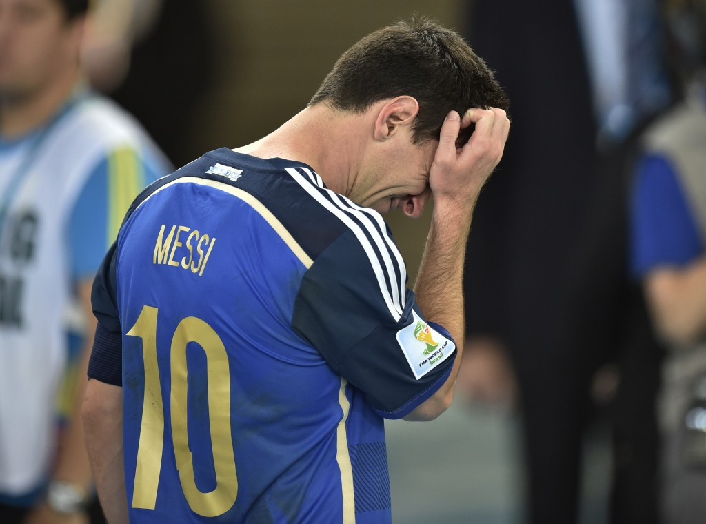 Argentina's Lionel Messi scratches his head as he goes to accept his runners-up medal after Sunday's World Cup final, in which Germany beat Argentina 1-0 and denied Messi the trophy he wanted most.