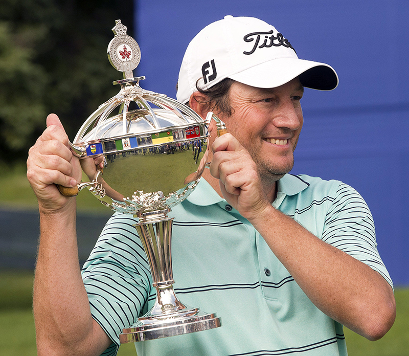 Tim Clark, from South Africa, holds his Canadian Open Championship trophy after final round play at the Canadian Open golf championship, Sunday. The Associated Press