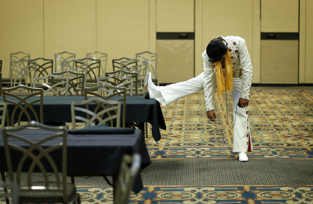 Elvis tribute artist Joseph Hall, of Branson, Mo., stretches before performing at the Las Vegas Elvis Festival in Las Vegas.