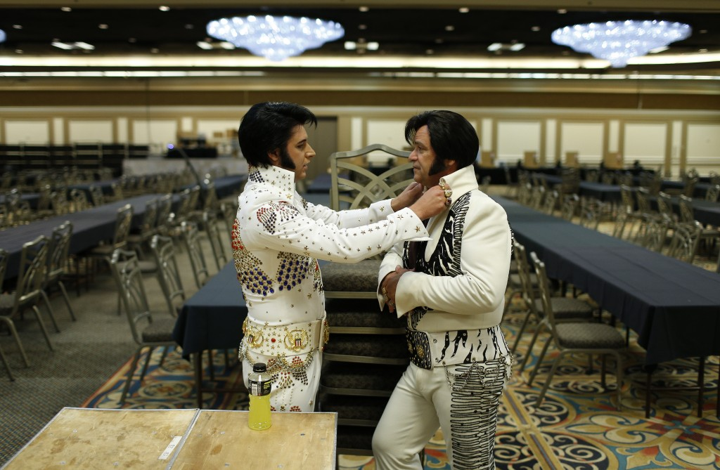 Frank Werth, left, of Hayes, Kan., straightens the collar of Tony Freitas, of Oakdale, Calif., during the Las Vegas Elvis Festival in Las Vegas.