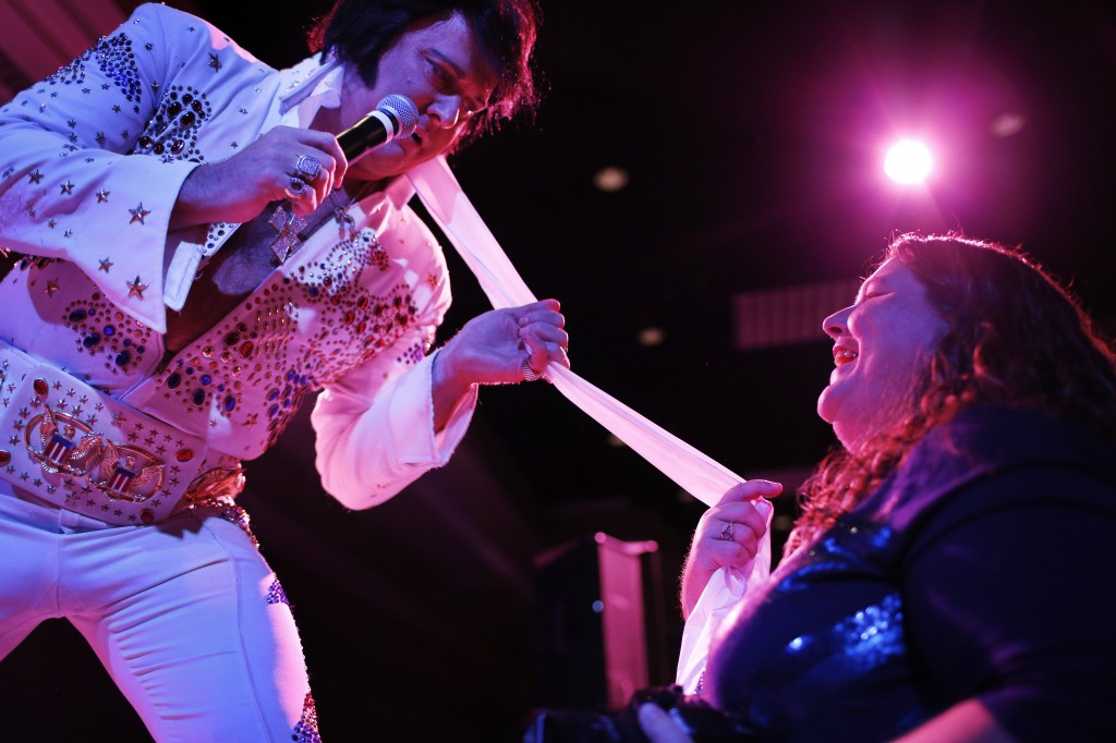 Elvis tribute artist Jim Westover, of Arizona City, Ariz., gives a scarf to fan Juanita Curtice, of Woodbridge, Va., during the Las Vegas Elvis Festival.