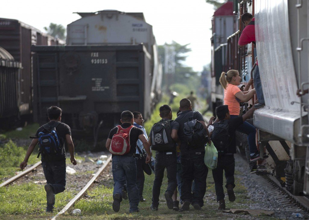 immigrants run to jump on a train during their journey toward the U.S.-Mexico border, in Ixtepec, Mexico, on July 12.