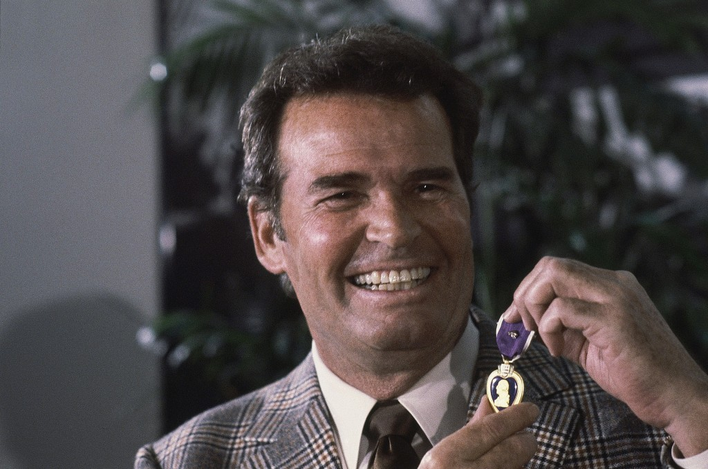 Actor James Garner, left, smiles as he holds up the Purple Heart medal presented to him in a ceremony in Jan. 24, 1983.  The Associated Press