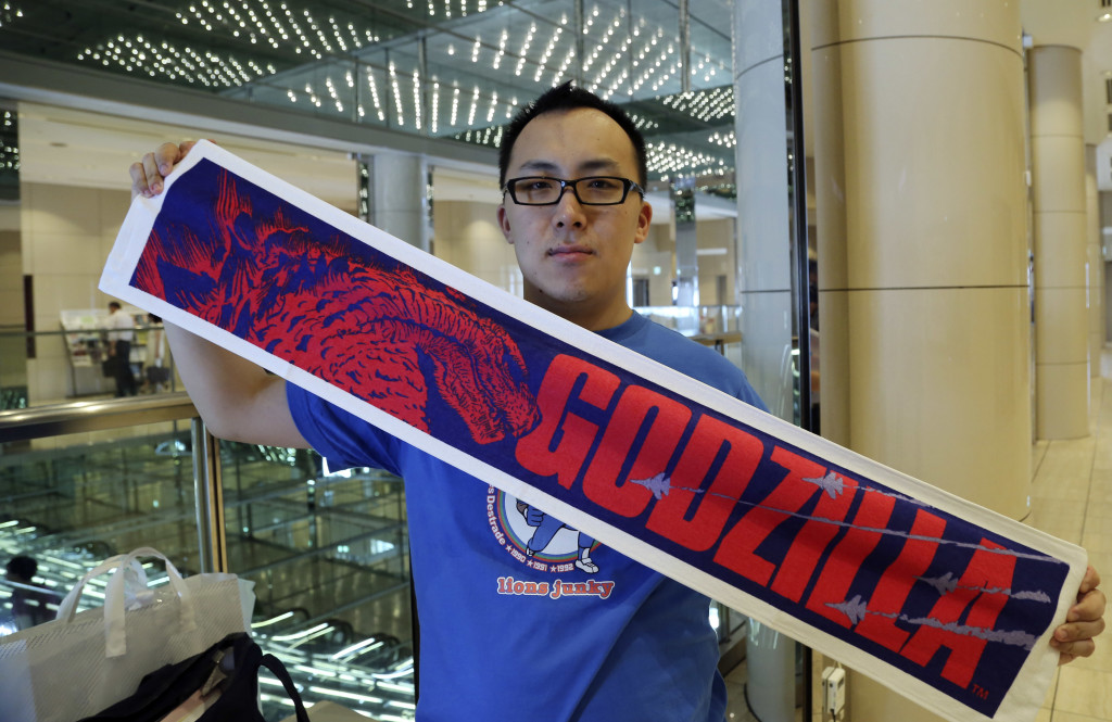 Yoshinori Nishizawa, 28, who lives in Tokyo and works in nursing, holds a Godzilla towel outside a movie theater in Tokyo on Friday.