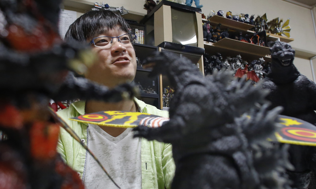 Takeshi Maruyama is surrounded by his collection of Godzilla and other monster figures at his apartment in Yokohama, near Tokyo.
