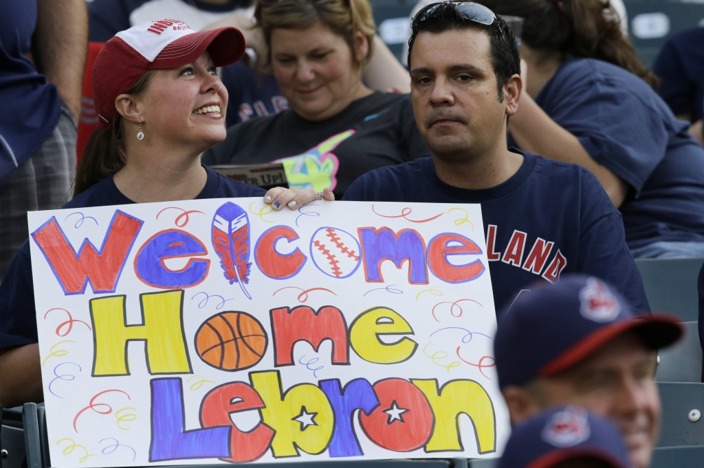 A Cleveland Indians fan holds a sign welcoming LeBron James back to the city, before Friday's baseball game between the Chicago White Sox and the Indians. Officials say James' return will mean hundreds of millions of dollars in economic benefit to Cleveland and Northeast Ohio.