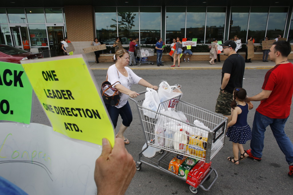 Demonstrators display placards outside a Market Basket grocery store as a shopper pushes a grocery cart on Tuesday in Chelsea, Mass. Supporters and employees rallied at Market Basket locations calling for Arthur T. Demoulas to be reinstated as CEO.