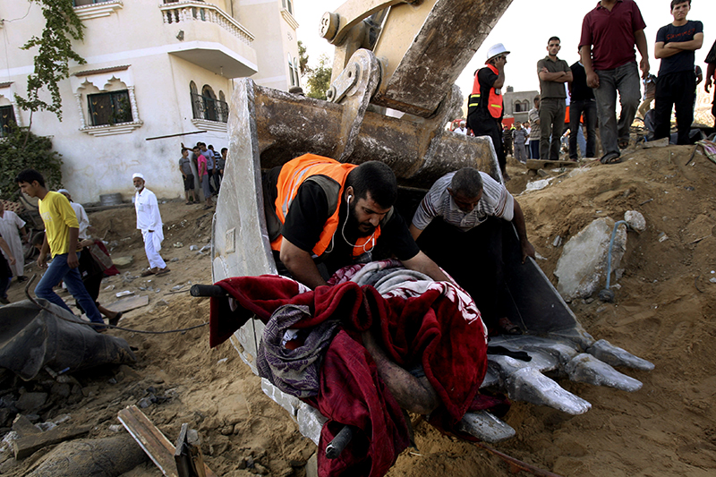 Palestinian rescue workers remove a body from the rubble of a building where at least 20 members of the Al Najar immediate and extended family were killed, including 10 children, by an Israeli strike according to Palestinian health official Ashraf al-Kidra, in Khan Younis, in the southern Gaza Strip, Saturday. The Associated Press