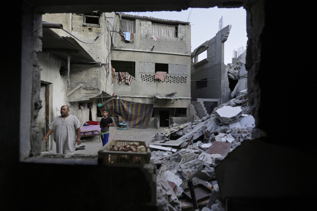 Palestinian Bajes Jendiyah, left, walks past the rubble of his family house, partially destroyed by an Israeli strike, in the Sabra neighborhood of Gaza City on Thursday. Israel and Hamas agreed Thursday to a 72-hour cease-fire starting Friday.