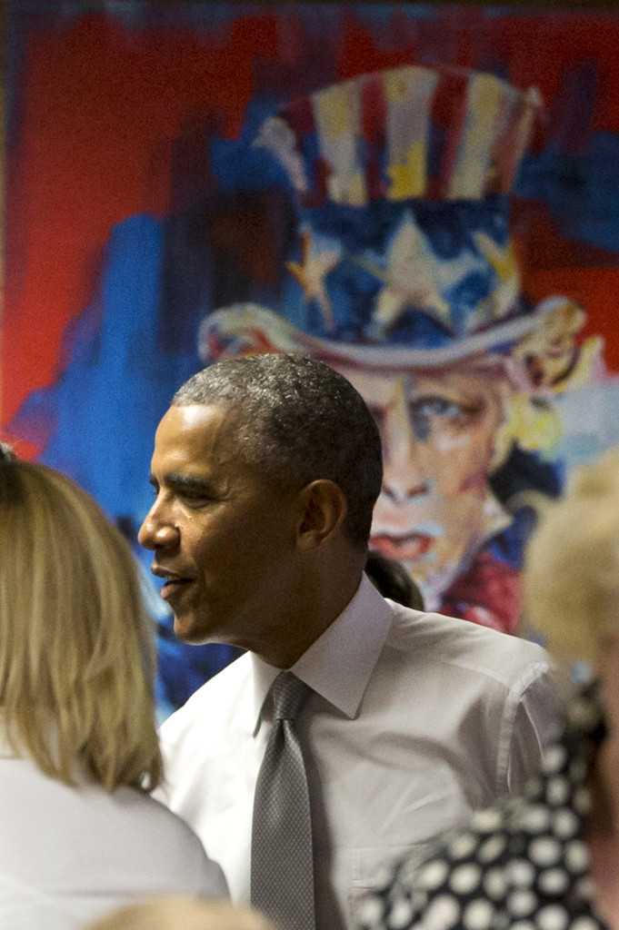 """President Barack Obama stands by a painting of """"Uncle Sam,"""" as he meets with workers at 1776, a hub for tech startups, Thursday, July 3, 2014, in Washington, where he spoke. The president said  job growth in June shows the recovery is taking hold, but the economy could still do better, he also urged Congress to work with him to help create more jobs."""
