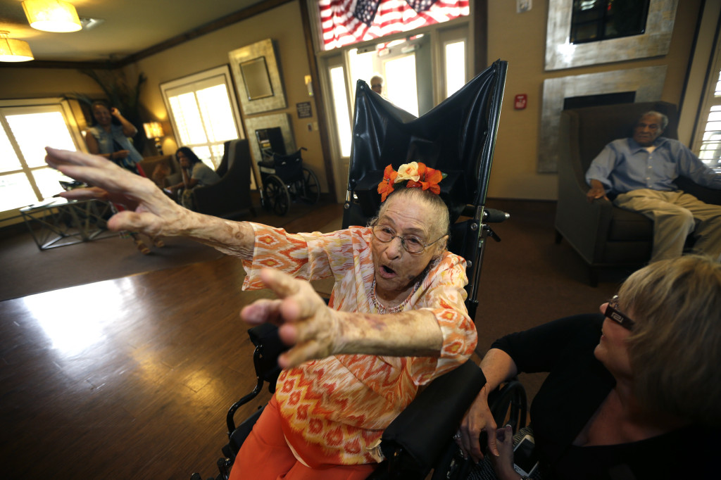 In this photo taken Thursday, July 3, 2014, Gertrude Weaver, who turns 116 July 4, raises her arms as she calls the hogs at Silver Oaks Health and Rehabilitation Center in Camden, Ark.