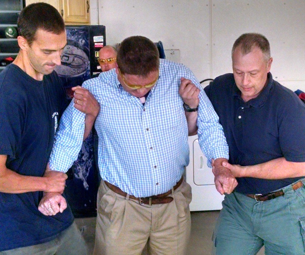 Fryeburg Selectman Paul Naughton is assisted by Bridgton police Officer Phillip Jones, left, and Fryeburg fire Lt. Mike McAllister while being Tasered during a certification program Monday.