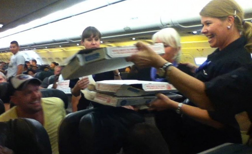 In this photo by a passenger and sent to KUSA-TV, a Frontier Airlines flight attendant passes out pizza to passengers aboard a Denver-bound flight diverted to Cheyenne, Wyo., Monday.  The Associated Press