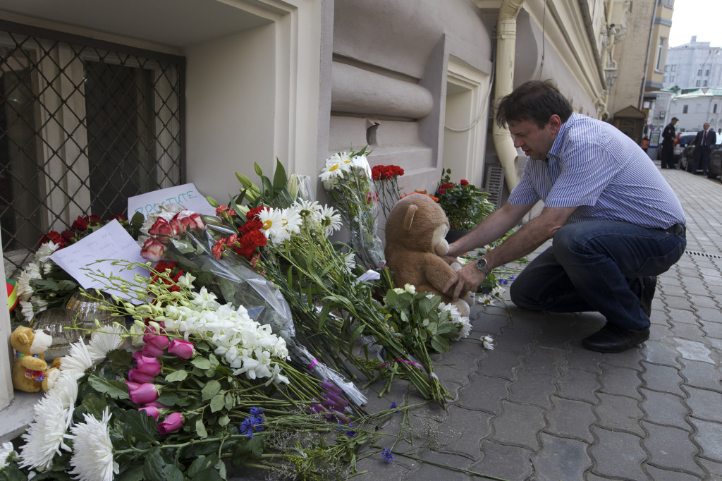 An unidentified man lays a stuffed bear among flowers outside the Dutch embassy in Moscow Friday. Rescue workers, policemen and even off-duty coal miners were combing a sprawling area in eastern Ukraine near the Russian border where the Malaysian plane ended up in burning pieces Thursday, killing all 298 aboard. The Associated Press