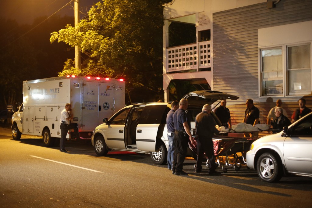 A body is moved from a Saco apartment complex where five members of a family, including three children, were found dead Sunday. The Associated Press/Robert F. Bukaty