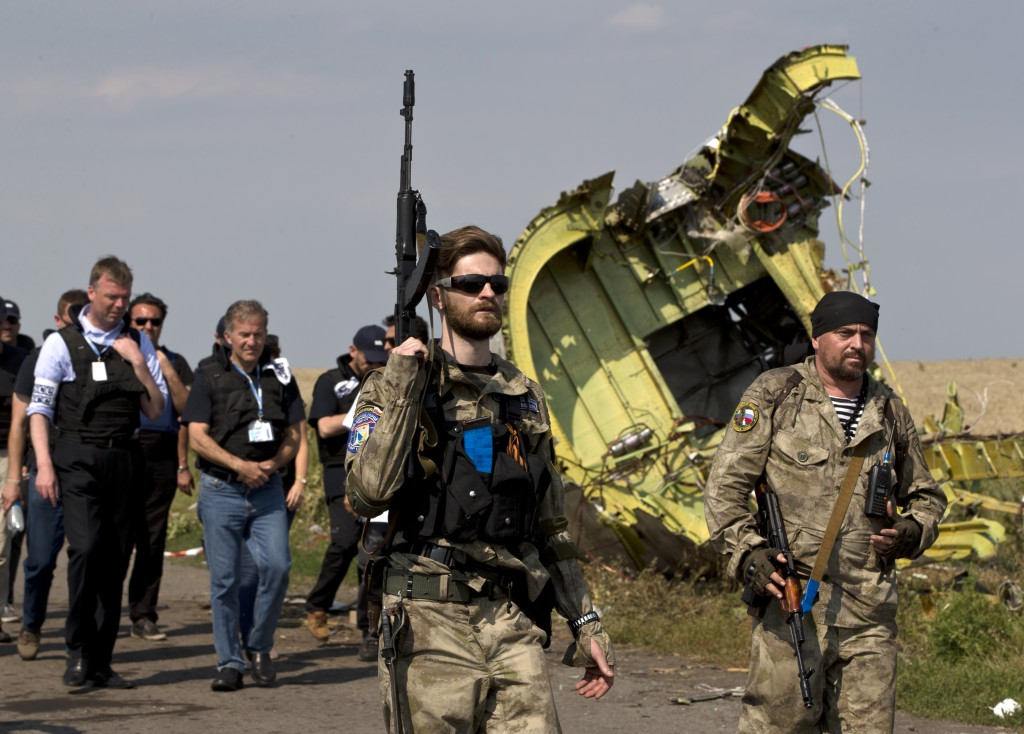 Pro-Russian rebels, followed by members of the OSCE mission, walk by plane wreckage as they arrive for a media briefing at the crash site of Malaysia Airlines Flight 17, near the village of Hrabove, eastern Ukraine, on Tuesday. A team of Malaysian investigators visited the site along with members of the OSCE mission for the first time since last week's crash.