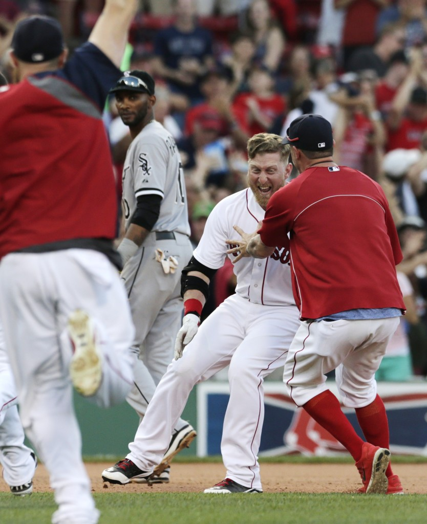 As Chicago White Sox shortstop Alexei Ramirez watches, Red Sox pinch hitter Mike Carp, center, is mobbed by teammates after his RBI single broke a 3-3 tie in 10th inning Thursday.